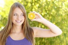 Jonge vrouw die aan Orangeslice kijkt Royalty-vrije Stock Afbeeldingen