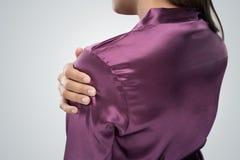 Jonge vrouw die aan pijn in schouder lijdt stock fotografie