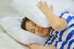 Jonge vrouw die aan slapeloosheid lijden en haar hoofd behandelen met een hoofdkussen Stock Foto's