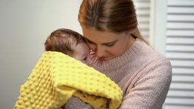 Jonge vrouw die aanbiddelijke pasgeboren baby knuffelen, die van familie voor goedgekeurd jong geitje houden royalty-vrije stock afbeeldingen
