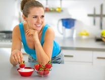 Jonge vrouw die aardbei met yoghurt eten Royalty-vrije Stock Foto