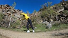 Jonge vrouw die acrobatische tik met landschap op achtergrond doen stock videobeelden