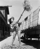Jonge vrouw die afgesneden jeans dragen en bij het landbouwbedrijf het werpen hooi in een wagen werken (Alle afgeschilderde perso stock foto's