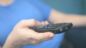 Jonge vrouw die afstandsbediening in woonkamer met behulp van stock video
