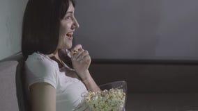 Jonge vrouw die alleen op een film in de avond met popcorn letten stock footage