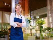 Jonge vrouw die als bloemist in winkel werkt royalty-vrije stock foto's
