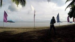 Jonge vrouw die als strandreinigingsmachine werken die draagstoelen, puin op tropisch zandig strand harken stock footage