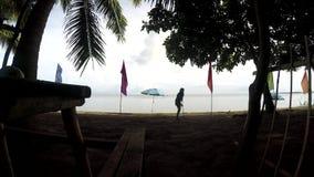 Jonge vrouw die als strandreinigingsmachine werken die draagstoelen, puin op tropisch zandig strand harken stock video