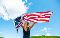 Jonge vrouw die Amerikaanse vlag op blauwe hemelachtergrond houden Verenigde Staten vieren 4 van Juli stock afbeeldingen