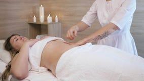 Jonge vrouw die anti-anti-cellulitebuikmassage in een salon van het schoonheidskuuroord hebben Een masseuse maakt cellulite massa stock footage