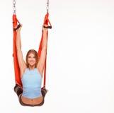 Jonge vrouw die anti-gravity luchtyoga binnen doen Royalty-vrije Stock Foto's