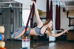 Jonge vrouw die antigravity yogaoefening uitvoeren stock fotografie