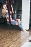 Jonge vrouw die antigravity yogaoefening uitvoeren royalty-vrije stock foto's
