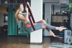 Jonge vrouw die antigravity yogaoefening uitvoeren royalty-vrije stock afbeelding