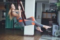 Jonge vrouw die antigravity yogaoefening uitvoeren royalty-vrije stock fotografie