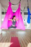 Jonge vrouw die antigravity yogaoefeningen met roze hangmat maken Stock Foto's