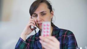 Jonge vrouw die arts over pillen roepen stock footage