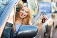Jonge vrouw die autosleutel toont Stock Foto's