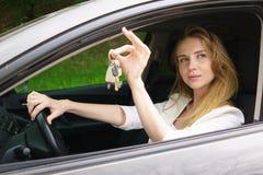 Jonge vrouw die autosleutel toont Royalty-vrije Stock Afbeeldingen