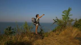 Jonge vrouw die backpacker foto met cellphone op bergpiek nemen stock videobeelden