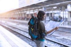 Jonge vrouw die backpacker kaart voor de planning van haar route voor RT kijken stock foto