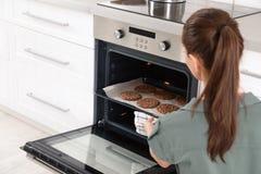 Jonge vrouw die bakselblad met koekjes van oven nemen stock foto's