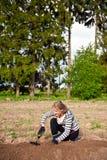 Jonge vrouw die bebouwing wiedt Stock Fotografie