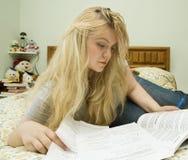 Jonge vrouw die in bed bestudeert Stock Fotografie