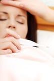 Jonge vrouw die in bed ligt dat haar temperatuur controleert Stock Foto's