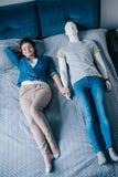 jonge vrouw die in bed met ledenpop perfecte verhouding liggen stock afbeelding