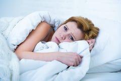 Jonge vrouw die in bed zieke onbekwaam aan slaap liggen die depressie en van de nachtmerriesslapeloosheid slaap aan wanorde lijde royalty-vrije stock fotografie