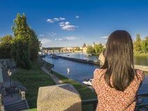 Jonge vrouw, die beeld met haar celtelefoon nemen van Legioenbrug met mening over Kampa-eiland, Vltava-rivier, het Kasteel van Pr stock afbeelding