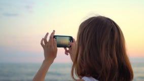 Jonge vrouw die beelden met smartphone op het strand nemen stock video