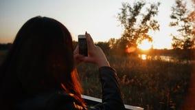 Jonge vrouw die beelden van zonsondergang op haar smartphone nemen stock videobeelden