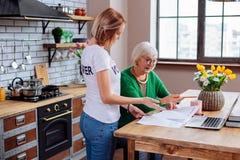 Jonge vrouw die bejaarde mevrouwpunten van achterstallig leningsbericht verduidelijken stock foto's