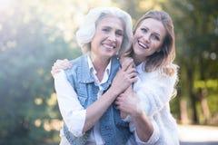 Jonge vrouw die bejaarde moeder in het park koesteren royalty-vrije stock fotografie