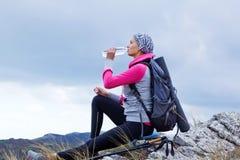 Jonge vrouw die in bergen wandelt stock afbeeldingen