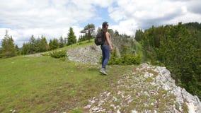 Jonge vrouw die in berglandschap wandelen stock videobeelden