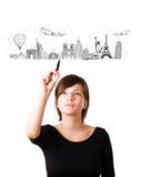 Jonge vrouw die beroemde steden en oriëntatiepunten trekken op whiteboard Stock Afbeelding