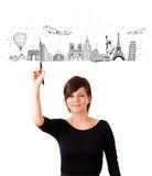 Jonge vrouw die beroemde steden en oriëntatiepunten trekken op whiteboard Royalty-vrije Stock Afbeelding