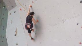 Jonge vrouw die bij binnen het beklimmen gymnastiekmuur uitoefenen Opleidende klimmers op de het beklimmen muur het meisje heeft  stock videobeelden