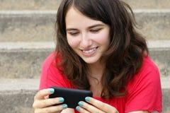 Jonge vrouw die bij celtelefoon glimlacht Stock Foto