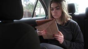 Jonge vrouw die bij de achterbank van een auto reizen stock videobeelden