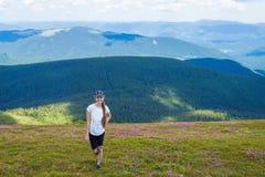 Jonge vrouw die bij de Bergentribunes van de Karpaten wandelen bovenop een heuvel Stock Fotografie