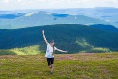 Jonge vrouw die bij de Bergentribunes van de Karpaten wandelen bovenop een heuvel Stock Afbeelding