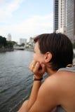 Jonge vrouw die bij de overkant van de rivier staart Stock Afbeeldingen