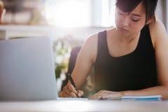 Jonge vrouw die bij haar bureau werken die nota's nemen stock foto's
