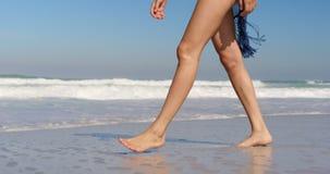 Jonge vrouw die bij strand in de zonneschijn 4k lopen stock video