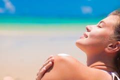 Jonge vrouw die bij strand zonroom op schouder zetten stock afbeeldingen