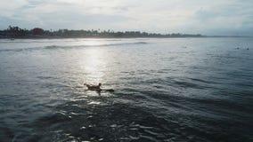 Jonge vrouw die bij surfplank in oceaan paddelen stock videobeelden